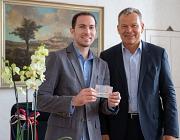 Oberbürgermeister Dr. Thomas Spies (r.) heißt Jacobo Antonio Wiesner Aragon in Marburg willkommen und überreicht ihm persönlich dessen Aufenthaltstitel. Der Amerikaner ist der 10.000 Mensch mit ausländischem Pass, der derzeit in Marburg lebt.