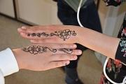2 Hände mit Henna-Tattoos werden nebeneinander gehalten.