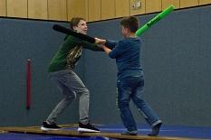 2 Jungen kämpfen mit Schaumstoffschwertern auf einer Bank.©Universitätsstadt Marburg