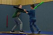 2 Jungen kämpfen mit Schaumstoffschwertern auf einer Bank.