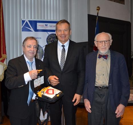 Oberbürgermeister Spies nimmt einen Automatisierten Externen Defibrillator vom stellvertretenden Vorsitzenden des Fördervereins Prof. Dr. Bernhard Maisch (l.) und dem ersten Vorsitzenden Prof. Dr. Hans Kaffarnik (r.) entgegen.©Milena Ceh, i.A.d. Stadt Marburg