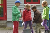 4 Kinder in Regenkleidung stehen um einen Eimer herum und scheinen etwas anzurühren.©Universitätsstadt Marburg