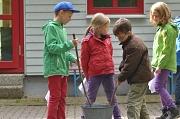 4 Kinder in Regenkleidung stehen um einen Eimer herum und scheinen etwas anzurühren.