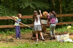 """4 Mädchen und Jungen bei der """"Arbeit"""" im Grünen, eine Schubkarre wird ausgeschüttet.©Universitätsstadt Marburg"""