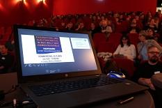Im Vordergrund ein Laptop, der für eine Präsentation vorbereitet ist. Im Hintergrund ein gut gefüllter Kinosaal.©Universitätsstadt Marburg