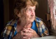 Ältere Frau schaut traurig aus dem Fenster.