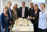 Die Mitglieder der Arbeitsgemeinschaft Stadthalle vor einem Modell wie die Stadthalle später aussehen soll - in der Mitte der Gruppe Oberbürgermeister Vaupel©Vanessa Veit