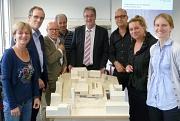 Die Mitglieder der Arbeitsgemeinschaft Stadthalle vor einem Modell wie die Stadthalle später aussehen soll - in der Mitte der Gruppe Oberbürgermeister Vaupel