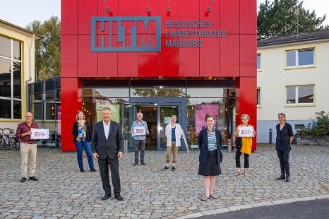 Anah Filou (v. l.) ist Marburgs erste Stadtschreiberin. Zum Auftakt des ersten Marburg800-Projekts hat Oberbürgermeister Dr. Thomas Spies (v. l.) die Wienerin zusammen mit Intendantin Carola Unser (r.) begrüßt. Hinten (v. l.) ein Teil des Marburg800-Teams©Jan Bosch