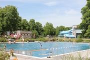 Schwimmer im Sportbecken ziehen ihre Bahnen. Im Hintergrund die Halle und die Rutsche.