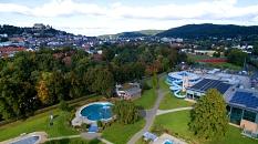 Luftaufnahme vom AquaMar mit dem Freibad und dem Hallenbadkomplex. Im Hintergrund das Universitätsstadion und die Altstadt von Marburg.©www.luftaufnahmen-drohnen.de