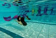 2 junge Mädchen mit Flossen als Meerjungfrau im Wasser schwimmend