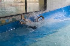 Mit Schwung ins Auflaufbecken: Ein Rutscher kommt mit hoher Geschwindigkeit aus der Rutsche. Das Wasser spritzt.