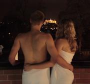 2 Personen im Bademantel blicken bei Nacht zum Schloss