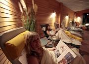 Frauen im Ruheraum der Sauna beim Zeitung lesen