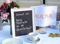 """Auf einem """"gedeckten Tisch"""" vor dem Erwin-Piscator-Haus machten die Mitglieder der Projektgruppe """"Familie und Armut"""" die verschiedenen Facetten des Themas Armut sichtbar.©Nadja Schwarzwäller i.A.d. Stadt Marburg"""