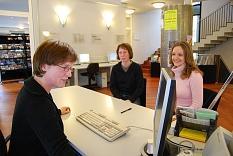 Eine Mitarbeiterin blickt auf einen Monitor an der Anmeldung. Zwei Kundinnen sitzen vor ihr.