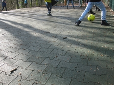 Fußballerbeine auf dem neuen Kautschukbelag des Ballspielfeld in der Kita Barfüßer Tor©Universitätsstadt Marburg FD Stadtgrün