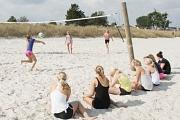 Im Vordergrund sitzen einige Jugendliche, die anderem beim Volleyball am Strand zuschauen.