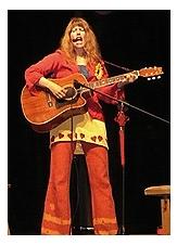 Die Sängerin Beate Lambert steht mit Gitarre auf der Bühne und singt in ein Mikrofon.©Beate Lambert