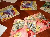 Große Memorykarten mit Zeichnungen, auf denen ein Mädchen in der Bücherei zu sehen ist, liegen auf dem Fußboden©Universitätsstadt Marburg