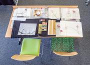 Blick auf einen Tisch mit Ergebnis eines Tuschemalkurses: Papier mit blumigen Tuschezeichnungen