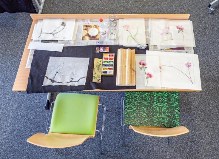Blick auf einen Tisch mit Ergebnis eines Tuschemalkurses: Papier mit blumigen Tuschezeichnungen©Oliver Reuther