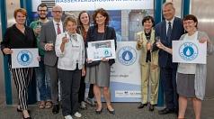 """Oberbürgermeister Dr. Thomas Spies (2.v.r.) und Stadtwerke-Geschäftsführer Dr. Bernhard Müller (3.v.l.) nehmen zusammen mit Vertreter/innen der Stadtwerke, der Stadt Marburg und der Studierenden das """"Blue Community""""-Zertifikat von Christa Heck (3.v.r.) en"""