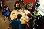 An einem runden Tisch sitzen 6 Leute und spielen ein Spiel, zu dem eine große Landkarte gehört.