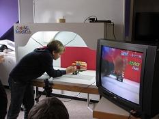 Ein Junge steht neben einem Tisch und bereitet die nächste Aufnahme für den animierten Lego-Trick-Film vor. Rechts steht ein Fernseher, in dem man das Geschehen ein zweites mal sehen kann.©Universitätsstadt Marburg