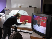 Ein Junge steht neben einem Tisch und bereitet die nächste Aufnahme für den animierten Lego-Trick-Film vor. Rechts steht ein Fernseher, in dem man das Geschehen ein zweites mal sehen kann.