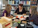 Drei Schülerinnen arbeiten in einer kleinen Arbeitsgruppe anhand verschiedener Gegenstände eine Performance aus.©Universitätsstadt Marburg