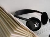 Kopfhörer liegt auf einem aufgeschlagenem Buch©Stadtbücherei Marburg