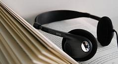 Kopfhörer liegt auf einem aufgeschlagenem Buch