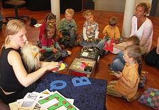 Kinder sitzen im Kreis vor einer geheimnisvollen Maschine, im Vordergrund die Bibliothekarin mit bunten farbigen Buchstaben©Universitätsstadt Marburg