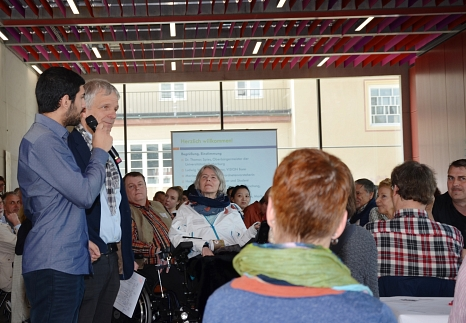 Moderator Ludwig Weitz (stehend 2. v. l.) interviewte Hadar Al-Saffar (l.), der stellvertretend für alle neuen Teilnehmer seine Motivation erklärte, sich für seine Stadt zu engagieren.©Stadt Marburg, Philipp Höhn