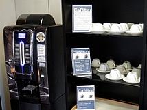 Der schwarze Getränkeautomat bietet verschiedene Kaffeesorten und andere Heißgetränke an. Im Regal daneben befinden sich Tassen und Espressotassen aus Porzellan.©Universitätsstadt Marburg