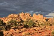 Dunkle Wolken über einer von der Sonne angestrahlten Bergkulisse eines Canyons