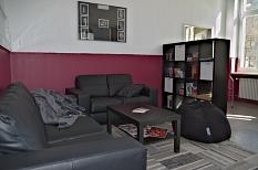 Die Wände sind im unteren Bereich nun bordeauxrot gestrichen, eine Sofaecke mit Tisch wird von einem Regal als Raumteiler eingrahmt.©Stadt Marburg