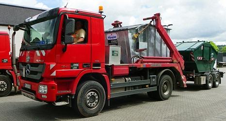 Das Foto zeigt ein Containerfahrzeug der MEG mit einer geladenen Absetzmulde und einer Weiteren auf einem Anhänger.©DBM, Sonja Stender