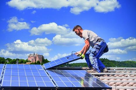 Zwei Männer installieren eine Photovoltaikanlage auf einem Dach. Im Hintergrund das Marburger Schloss.©Adobe Stock © mmphoto, Adobe Stock © Circumnavigation, Layout: mr//media GmbH