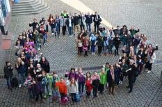 Zahlreiche Mädchen und Erwachsene bilden auf dem Markplatz ein G.©Universitätsstadt Marburg