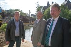 Bürgermeister Wieland Stötzel (von rechts), DBM-Betriebsleiter Joachim Brunnet und Bernhard Ivo (DBM) schauen sich die Arbeiten an der Weidenhäuser Brücke an. Im Hintergrund befüllen Arbeiter die Verbaukästen aus Holz mit Lehm.©Stadt Marburg, Patricia Grähling