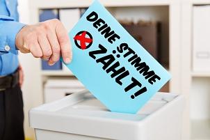"""Einwurf eines Stimmzettels mit de Aufschrift """"Deine Stimme zählt"""" in eine Wahlurne©Fotolia"""