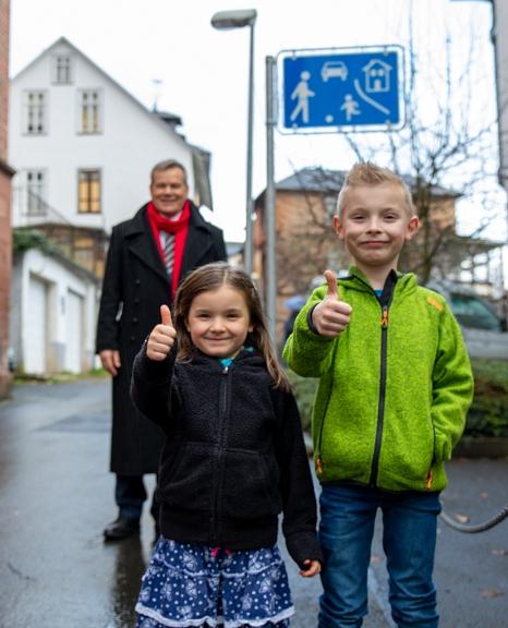 Der achtjährige Franz Ellenberger und seine fünfjährige Schwester Karla freuen sich mit Oberbürgermeister Dr. Thomas Spies darüber, dass das Sauersgässchen nun eine Spielstraße ist und die Stadt damit einem jungen Bürger einen Wunsch erfüllt hat.©Patricia Grähling, Stadt Marburg