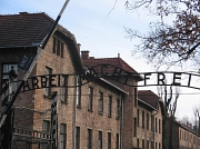 """Der Eingangsbereich zum Konzentrationslager Auschwitz mit der Aufschrift """"Arbeit macht frei""""."""