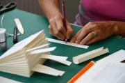 Detailaufnahme Hände, die auf Papier schreiben, im Vordergrund gefaltetes Papier in Buchform, Kurs Monika Jäger 2019