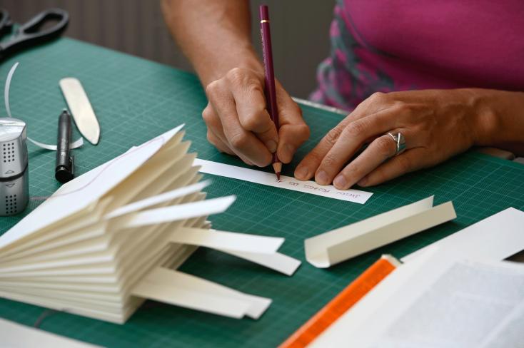 Detailaufnahme Hände, die auf Papier schreiben, im Vordergrund gefaltetes Papier in Buchform, Kurs Monika Jäger 2019©Georg Kronenberg
