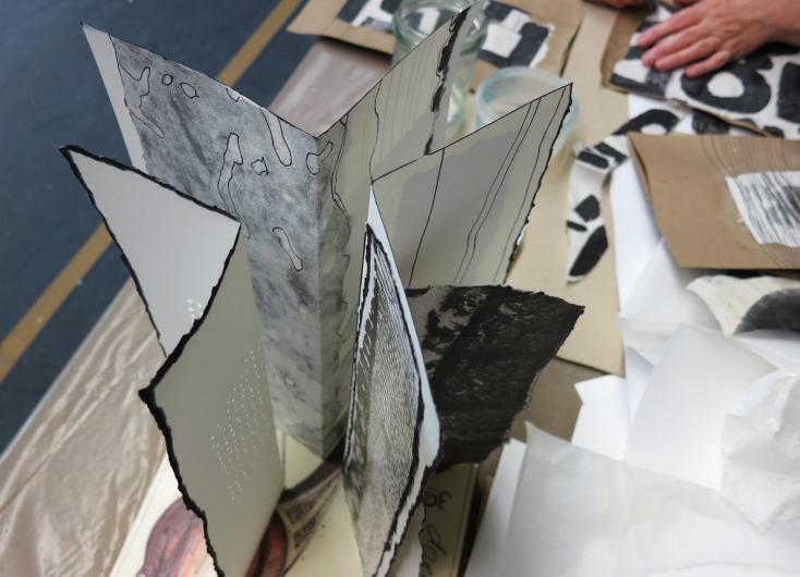 Detailaufnahme Papierkonstruktion mit bemalten Blättern in Schwarz-Weiß, die gefaltet nebeneinander stehen©Uta Schneider