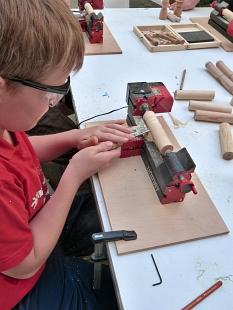 Ein Junge arbeitet an einer Drechselmaschine, er trägt eine Schutzbrille©Universitätsstadt Marburg